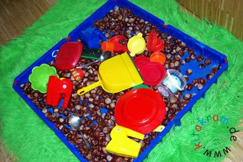 Dieses Beispiel zeigt ein Sandbecken aus Kunststoff, gefüllt mit Kastanien.