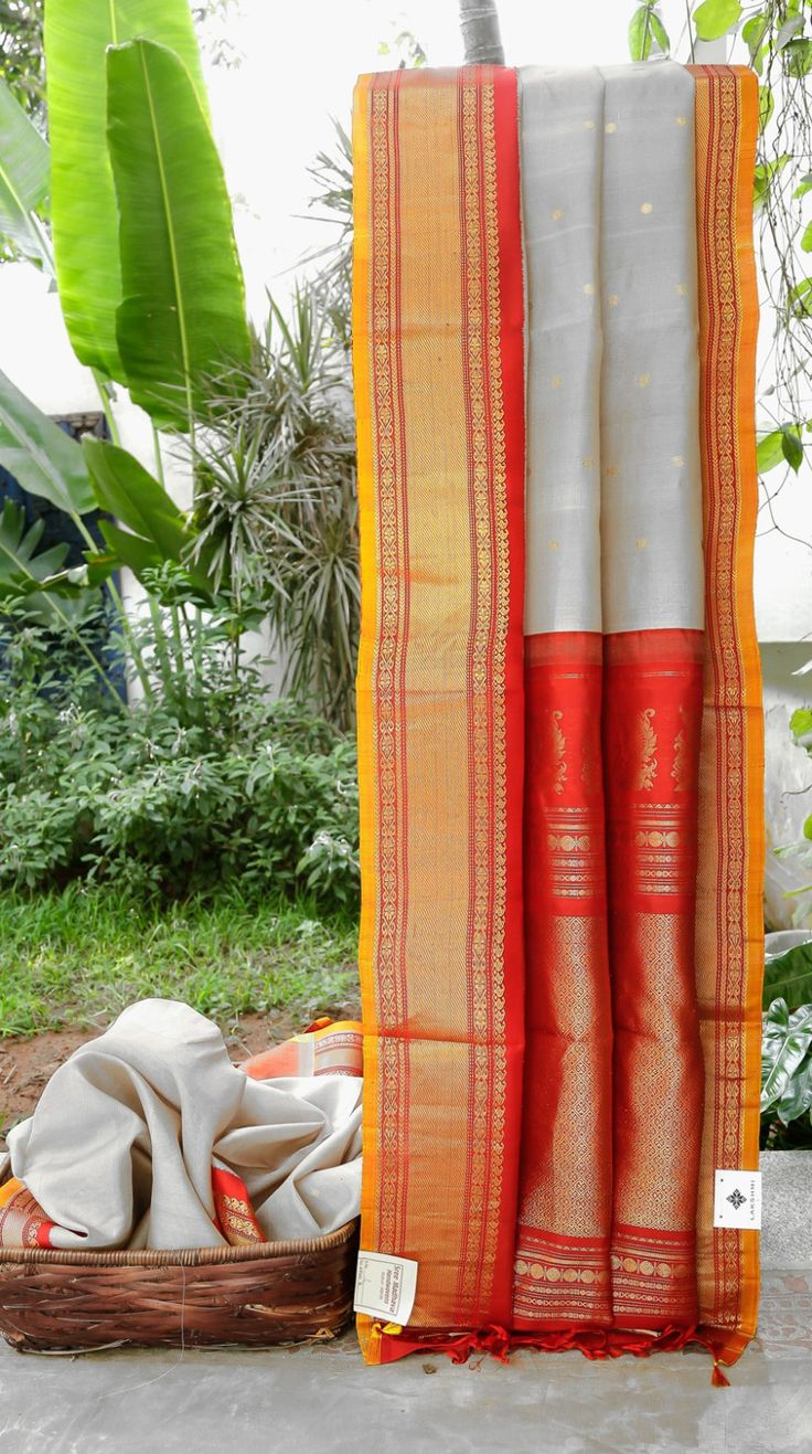 This gadwal tussar is in cloud ash with round gold zari bhuttas. The border and pallu are in blood red with gold zari work and gold yellow selvedge at the borders giving it a light and bright finis…
