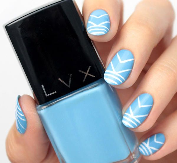 Create this statement nail art with a soft blue base coat and a white geometric design you can freehand on each of your nails.