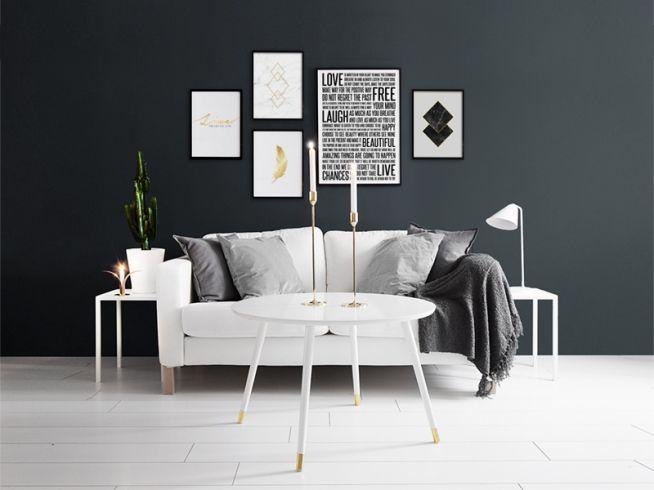 Tavelvägg med posters i svarta ramar mot svartmålad vägg. Svartvit inredning. Snygga inredningsdetaljer.