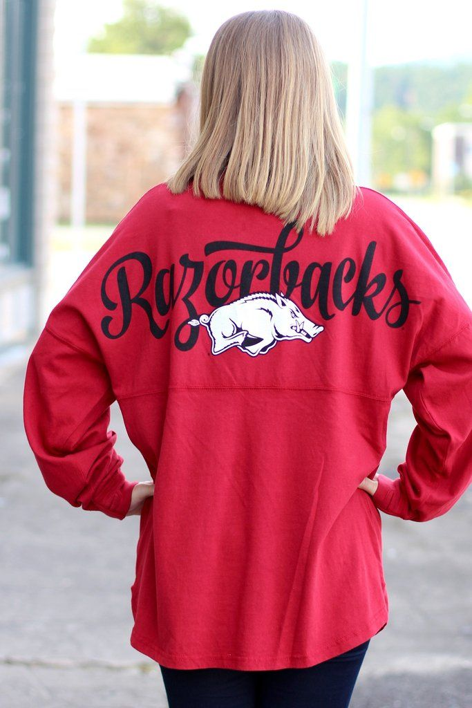 "Arkansas Razorback jersey featuring a front left chest Hog logo and a Glitter hog on the back with ""Razorbacks"" in script across it. Deep red in color with black graphics and white glitter Hog."