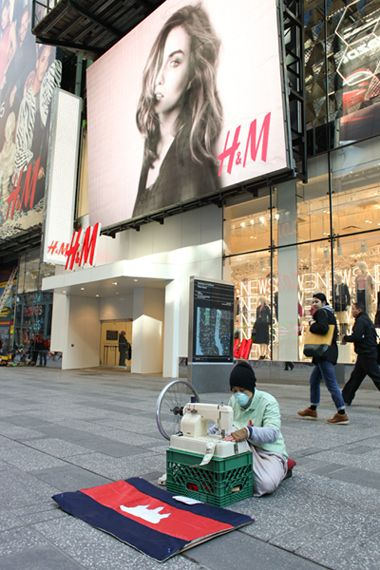 """Performance protest (2014): """"On a freezing Friday in January, Khmer-American artist Kat Eng sits in front of retail giant H&M's Time Square store working on a manual sewing machine. For eight hours, Eng stitches together U.S. dollar bills while wearing a surgical mask and bloodstained shirt. Her performance ... protests the way fast fashion and consumer culture creates oppressive conditions for Khmer workers."""""""