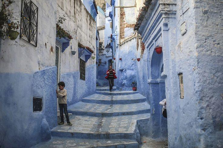 Ένα ντόπιο αγόρι και ένας τουρίστας περιφέρονται στη γραφική Μεντίνα της πόλης Chefchaouen στο βόρειο Μαρόκο, γνωστής για τα βαμμένα γαλάζια σπίτια και σοκάκια