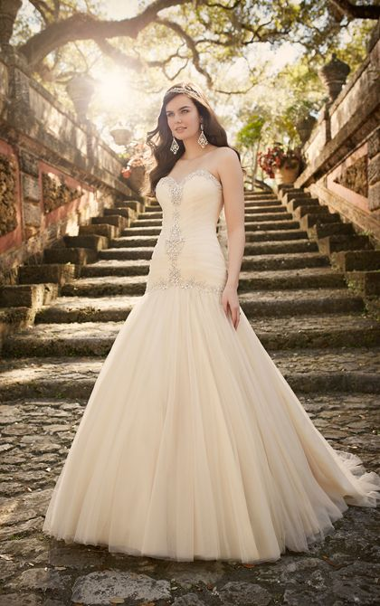 This elegant tulle over satin bridal gown from the Essense of Australia wedding dress collection boasts Diamante beading on its sweetheart neckline down the front of its ruched bodice and around its drop waist. The ethereal tulle skirt falls elegantly to the floor into a chapel train.