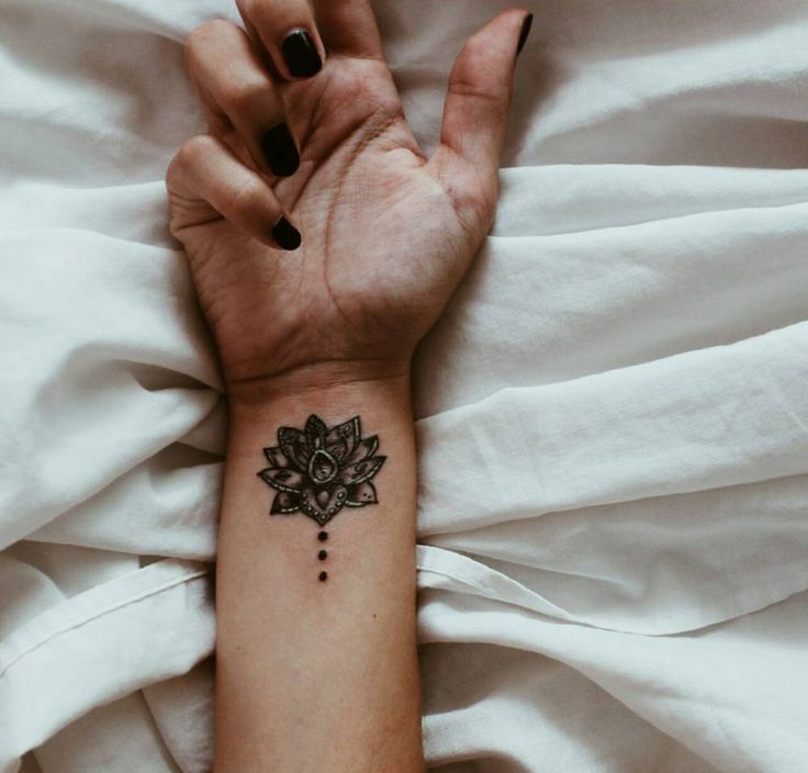 Lotus tattoo on the right inner wrist.