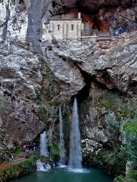 Santa Cueva de Covadonga is a Catholic sanctuary in Asturias, Spain in a cave of the Picos de Europa mountains.  The original structure dates to the 8th century, but the original wood carvings were lost in a fire.  The carvings were replaced in the 18th century.  by  Nene 0 hidratoso