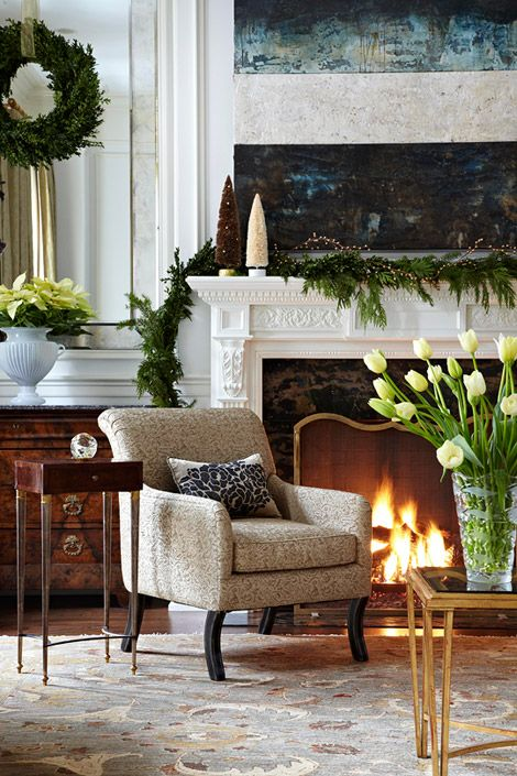 Furnished in traditional style but with clean lines and nothing fussy, this living room welcomes Christmas with a swag of greenery, natural branches, and pinecone trees on the mantel. A wreath of greenery and vases of white tulips and poinsettias accentuate the seasonal decor.