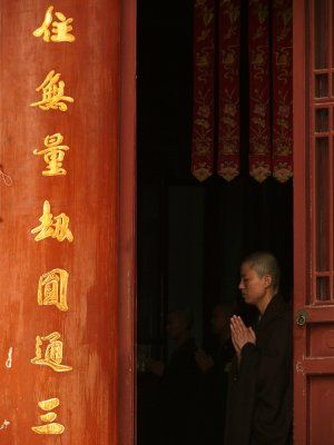 Prayers, Ji Ming Temple, Nanjing, China, 2007  I used the temple doorway as context for this image of a Buddhist nun at prayer.  There is a spiritual inscription on the door panel, and the dimly illuminated banners hanging in the darkness over the nun's head echo its vertical flow.