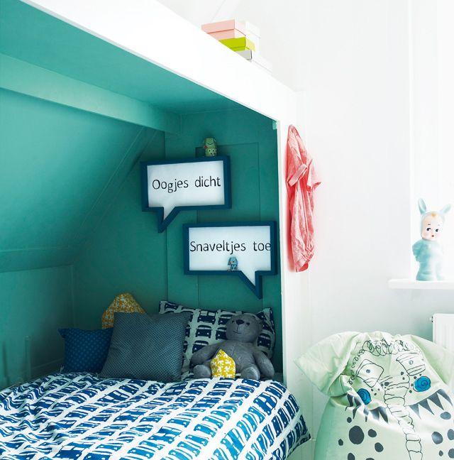 Een knus hoekje om te slapen, de rest van de kamer is wit waardoor het slaapgedeelte heel intiem aanvoelt.