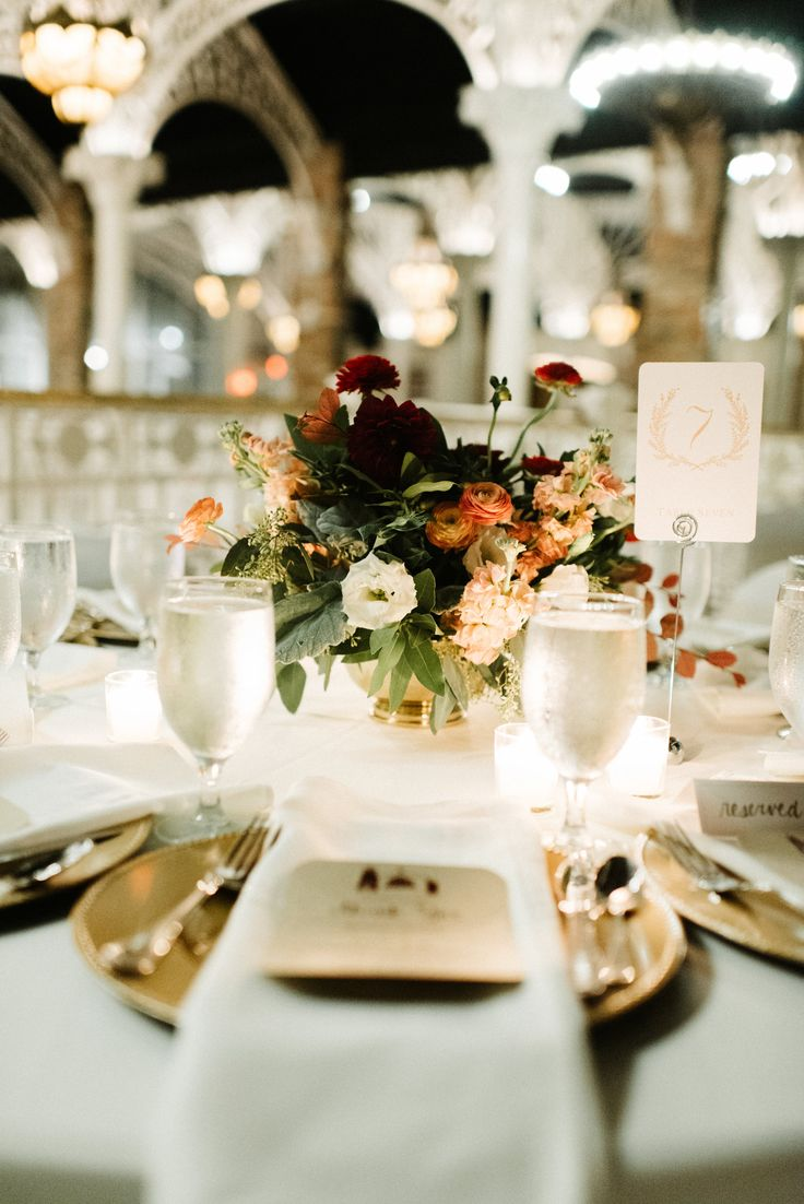 low wedding reception centerpiece of peach stock burgundy dahlia burgundy ranunculus peach