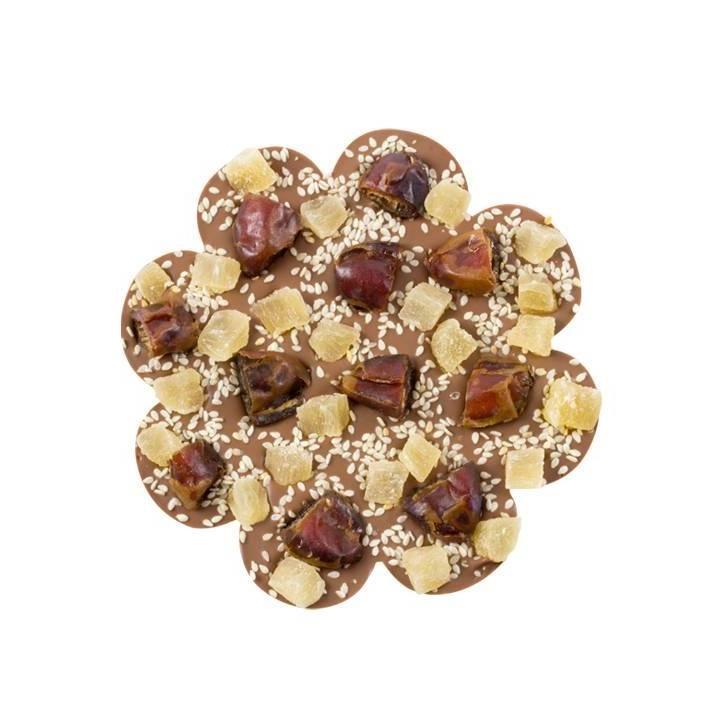 MLECZNA CZEKOLADA Z DAKTYLAMI Do aksamitnie mlecznej tabliczki czekolady w kształcie kwiatka dołożyliśmy daktyle suszone, ananasa w kostkach a całość posypaliśmy chrupiącym sezamem.