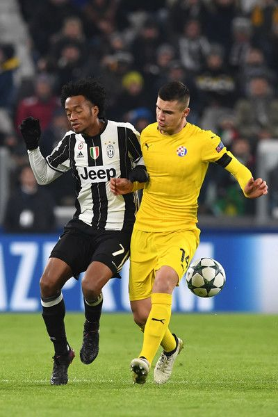 Juan Cuadrado (L) of Juventus clashes with Amer Gojak of GNK Dinamo Zagreb during the UEFA Champions League Group H match between Juventus and GNK Dinamo Zagreb at Juventus Stadium on December 7, 2016 in Turin.