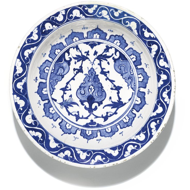 An Iznik blue and white pottery dish, Turkey, circa 1560-80 of deep round form with everted rim, decorated in underglaze cobalt blue, featuring a stylised arabesque in the centre emanating foliate scrolls, surrounded by lobed archways, the rim with floral vine, exterior with Chinese-style floral stems, old collection label to underside 31.4cm. diam. sotheby's