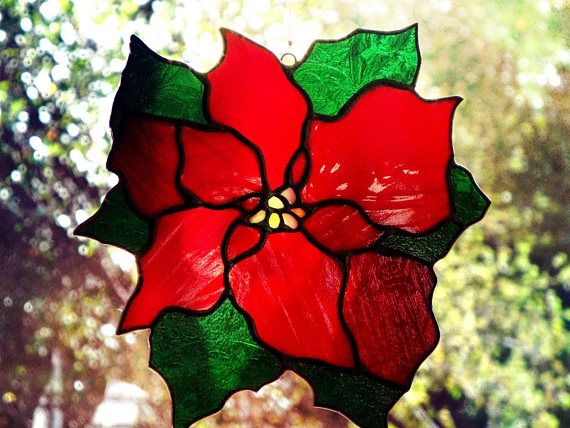 Stained glass Poinsettia Suncatcher, perfect to brighten up any window in your home for the holidays. Two tones of wispy red glass were used to create a look of depth for the flowers petals and the leaves are a green glue chip glass that looks like frost on the window in the