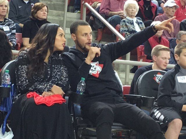 "CHARLOTTE, N.C. — Warriors star Stephen Curry looks at a jersey with his name and high school basketball number, during a halftime ceremony at his former high school in Charlotte, North Carolina. Curry's high school retired his number while Davidson College will honor him by renaming a section of its arena ""Section 30."""