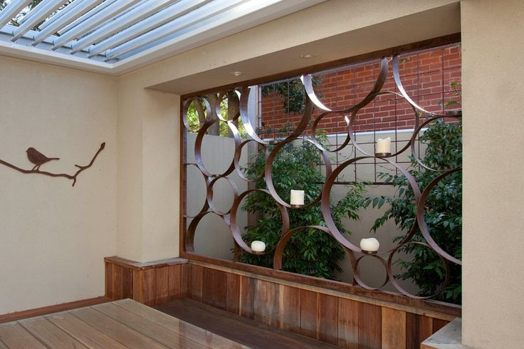 Decorative metal art garden screen. Hand-rolled steel in a rust finish with candle holders