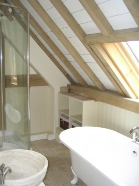 Cosy bathroom built under exposed oak roof