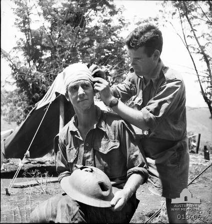 1942-11-19. New Guinea. Kokoda. Queenslander Pte. S. Wilson receives medical attention after a two days walk. He was wounded at close quarters. A Japanese bullet tore its way through the front of his helmet and out the back, wounding him slightly. (Negative by G. Silk).