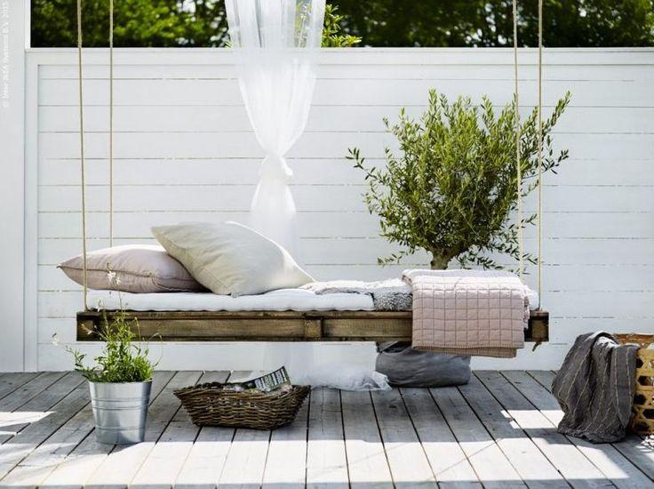 En hängande hammock av lastpall, som en dröm under ett altantak