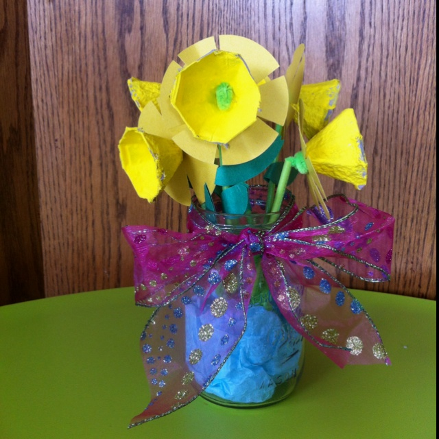 Egg Carton daffodil bouquet! You'll need yellow tempra paint, 1 mason jar, a glue stick, blue tissue paper, egg carton, green and yellow construction paper, green straws and green pipe cleaner. Optional ribbon for around the mason jar; and scissors to cut the shapes.  I just bent the pipe cleaner on either side of the flower and put the straw around the outside to keep it from falling over. Glue the leaves to the straw and put them in the mason jar!