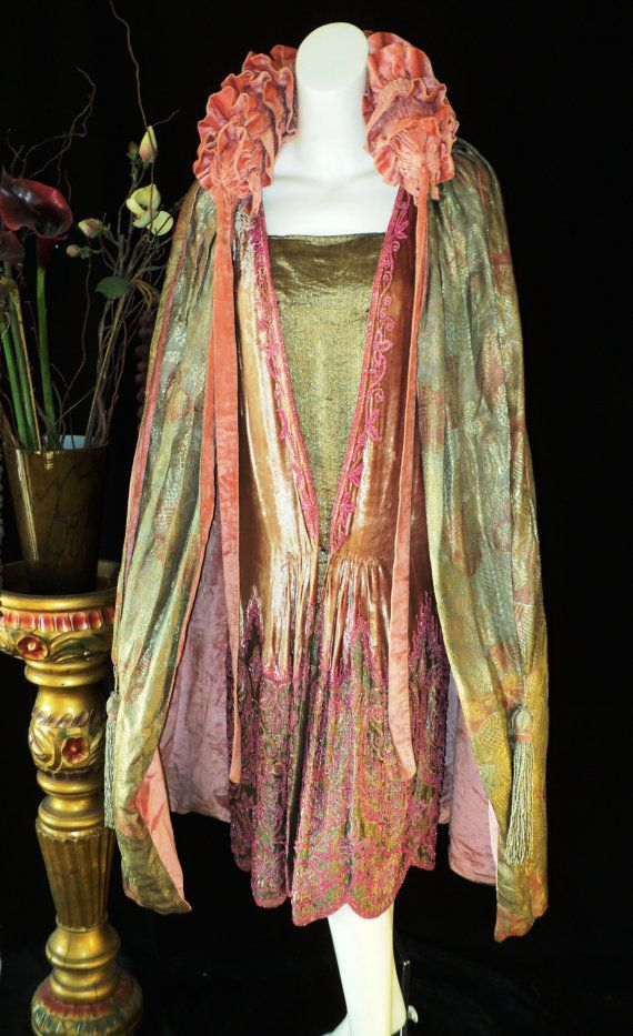 Antique Art Deco Pastel Metallic Lame Cocoon Cape Ruched Velvet Collar 1920s Flapper Opera Cape. The lame is a fabulous color combination of metallic golds, silvers and light pink tones. The lining is a luscious blushy pink velvet as well as the highly dramatic ruched collar. There are long velvet ties with encrusted beaded fringed tassels cascading down the fie. (hva)
