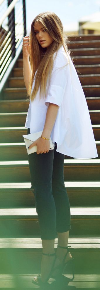 Street Style 2015: Kristina Bazan is wearing a white oversized shirt with a pair of ash grey trousers, black heels and a creme clutch bag