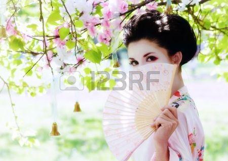 Aziatische stijl portret van jonge vrouw met ventilator in de bloeiende tuin Stockfoto
