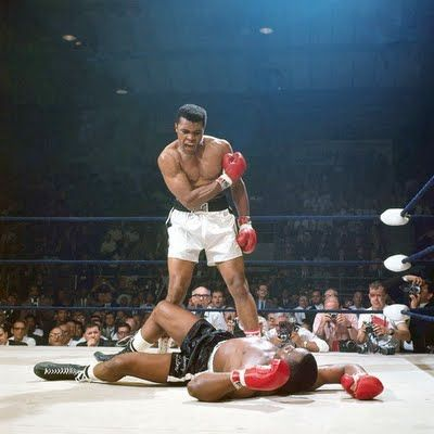Muhammad Ali looms over Sonny Liston after stinging him like a bee