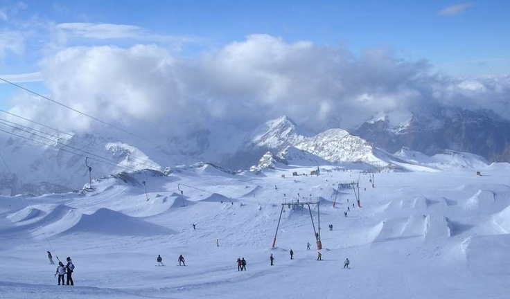 Les Deux Alpes.  Great skiing pretty much all year round, with fun cruising blues and challenging reds.