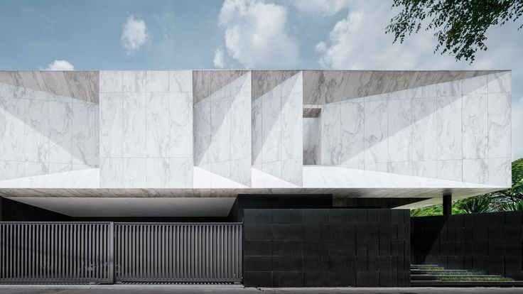 Wedge-shaped chunks are carved out of the marble-clad volume of this top-heavy house in Bangkok, Thailand, which was designed by local studio Openbox Architects.