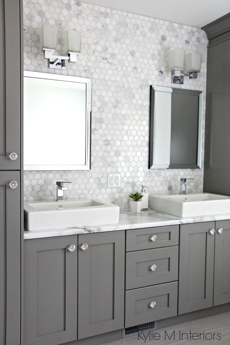 Entire wall tiles behind sinks.  Marble backsplash in hexagon shape with vanity cabinets painted Chelsea Gray, double sinks and chrome accents by Kylie M Interiors