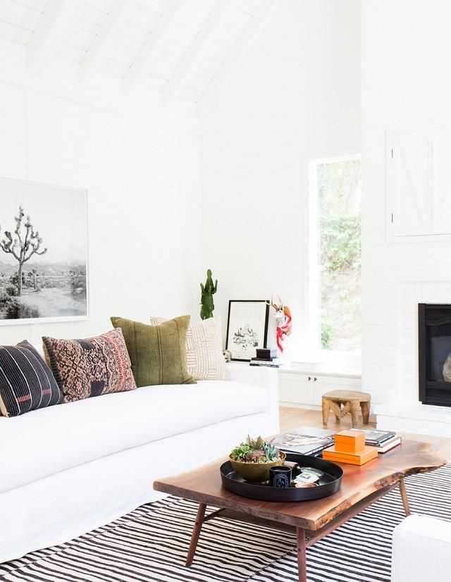 Style idea: use white walls and a white couch to keep a space feeling clean and open and then add concentrated pops of organic color via vintage textiles, throw pillows, and organic wood to add a bohemian and eclectic vibe to the space, and give it a family-friendly lived-in feel. See more of this California Eclectic Home by Amber Interiors on My Domaine!
