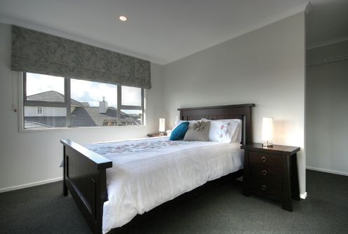 Walk in wardrobe behind the head of the bed in this guest suite bedroom