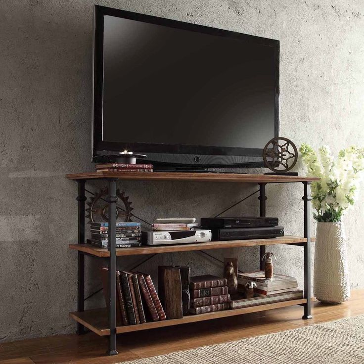This Myra TV stand has a weathered and timeworn patina allowing traces of natural wood and original colors to show through. A stylish black sand metal frame houses shelves that provide plenty of storage for a DVD player, books and magazines.