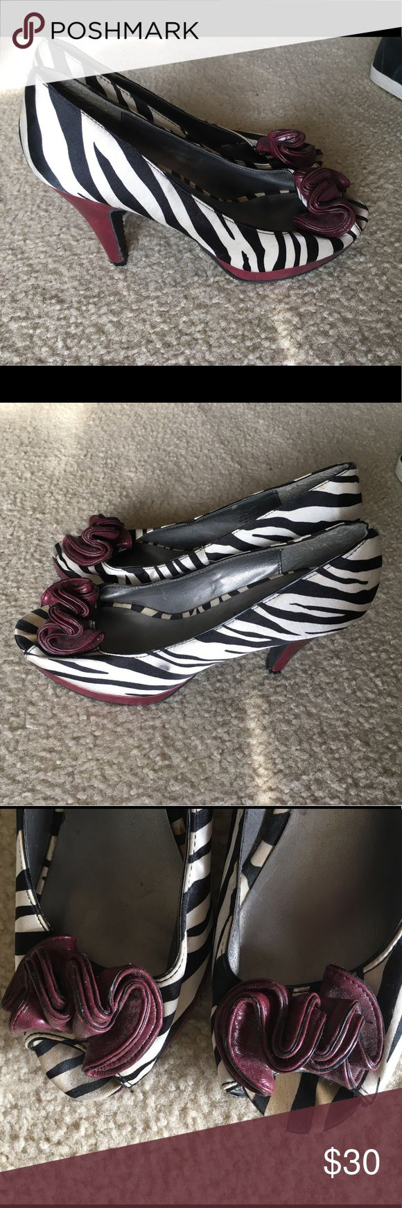 """Madden Girl Striped Zebra Heels Amazing striped heels with a maroon flower and maroon heels. Make a statement anywhere you go with these bad girls!  Heel height is 4"""". Size 10. The sole is sturdy even if you live in a colder climate. A few minor blemishes which you can see in the pics. Nothing's visible from the outside but one black smudge on the left shoe. I've probably worn them 3 times! Happy looking! Madden Girl Shoes Heels"""