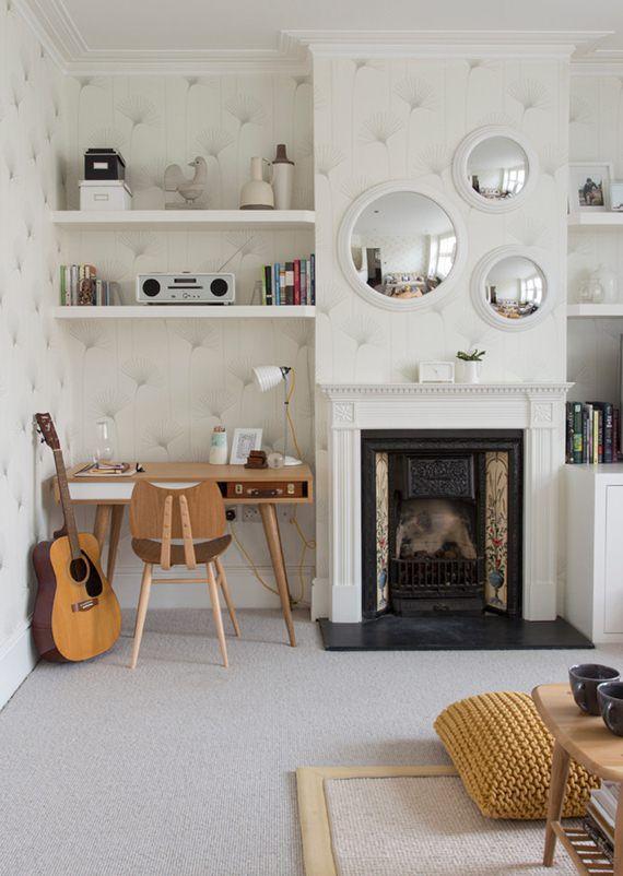 O papel de parede trouxe movimento para a sala, e os espelhos côncavos em cima da lareira ampliam o ambiente e decoram de forma inusitada. O mini home office também tem seu charme, com direito a prateleiras e espaço para o violão.
