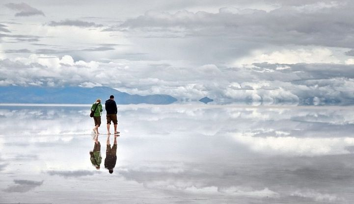 Salar de Uyuni Salt Flat in Bolivia - salt flat has a reflective surface that makes it seem like you're strolling through the sky. Giving the illusion that you're walking on water, the slated terrain claims to be the world's largest salt flat at approximately 4,000 square miles. To experience this, you must take a four-day off-road trip from the town of Uyuni to the Chilean border. Then, expect a long drive to the center of the salt lake. The pockets of dry salt turn the land into a giant…
