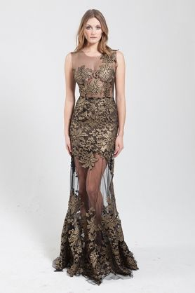 Gold coated lace and black mesh gown with all round sheer skirt. The Flora dress is made from a  black sheer mesh and is carefully embellished with gold coated lace cut outs. It has a one shoulder illusion created by the lace cut outs. This dress is designed as a slim fit with a round sheer skirt. The mesh section in the skirt allows the legs to be visable and creates a sexy yet stunning look. #evening #shoulderdetail #goldshoulderdetail #goldfloralpattern #skirtdetail #gold #elegant #NARCES
