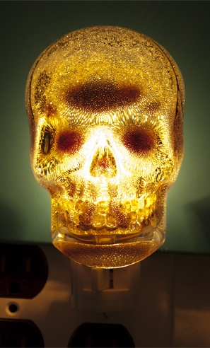 """SKULL NIGHT LIGHT    Light up your dark halls with the Skull Night Light! No need to to scared of the dark when you have this grinning skull in an outlet. Plugs into a standard 120 volt outlet. Bulb included.  4"""" tall    $12.00: Grinning Skull, Night Lights"""