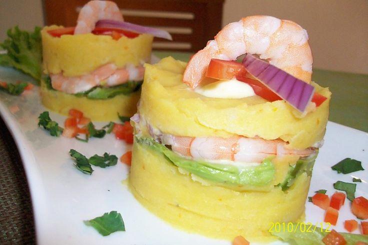 Causa camarón: Papa prensada, aliñada cubriendo un relleno a base de camarones con mayonesa y paltas.
