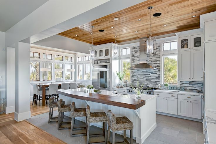 Modern beachy kitchen design with wood plank ceiling, blue & gray linear glass tiles backsplash, floor to ceiling white cabinets, sink in kitchen island, marble countertops, butcher block breakfast bar and seagrass counter stools. More info on Houzz: http://www.houzz.com/photos/1519117/Ponte-Vedra-Residence-contemporary-kitchen-jacksonville