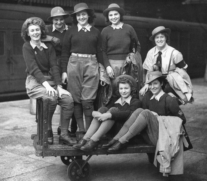 Land Girls at a London station before leaving for Kent.