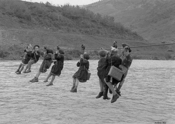 1959 - A scuola in carrucola Un gruppo di bambini con grembiuli e cartelle attraversa il fiume Panaro a Guiglia, vicino a Modena, per recarsi a scuola. Sono gli abitanti di due frazioni, Barletta e Castellino, che per andare a scuola devono attraversare il Panaro scorrendo lungo una corda d'acciaio tesa sul fiume.