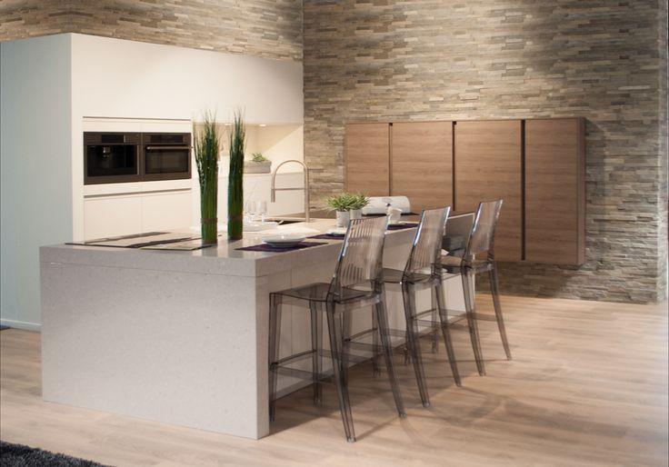 Design keuken met ingewerkte keukenkasten.  De keukenkasten van deze moderne designkeuken zijn volledig ingewerkt in de muur. Door de stenen muurafwerking komt de keuken nog meer op de voorgrond te staan. De zwevende kasten verdwijnen ook half in de muur waardoor er extra veel ruimte wordt bespaard. Het kookeiland is ook voorzien van een toog waardoor er kan gegeten worden aan het keukeneiland.