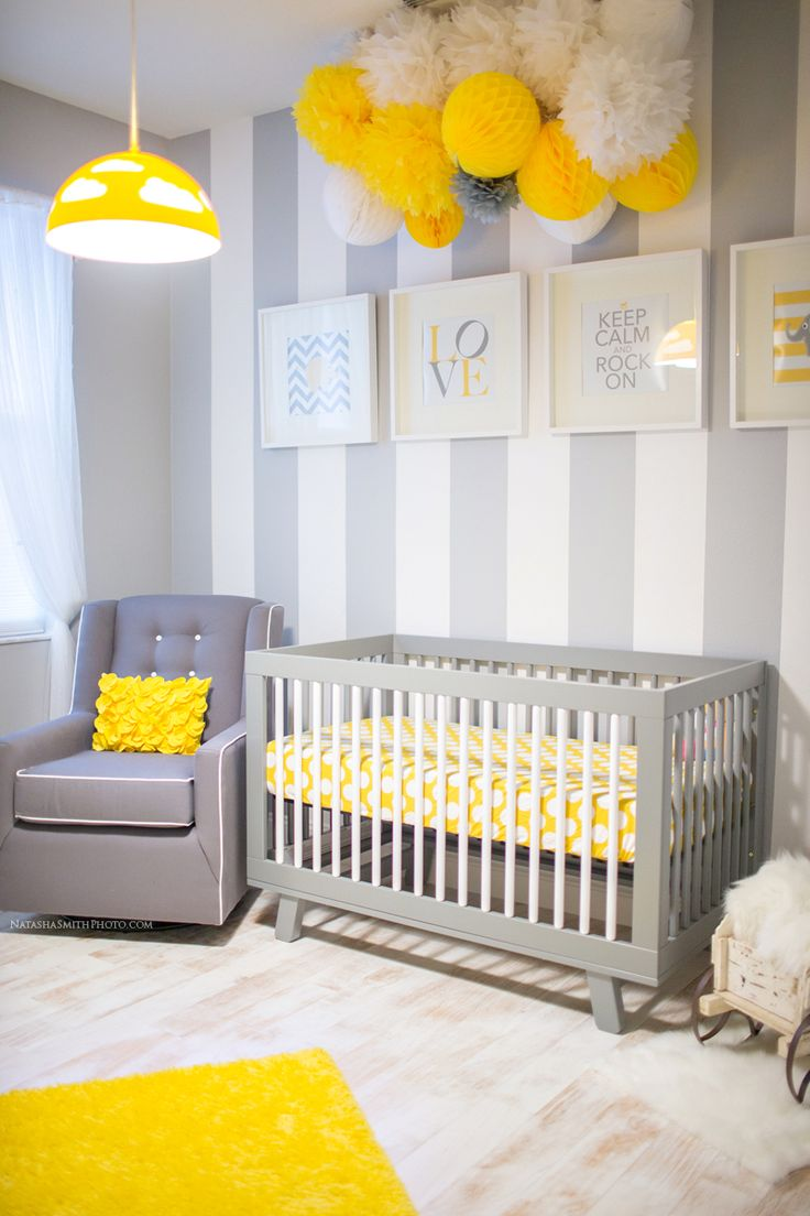 Light  Ikea, grouping of different tissue balls and poms above the crib,  gray and white striped walls, color and theme matched DIY wall art, ...