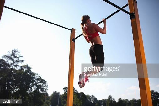 Stock Photo : Girl training on chin-up bar outdoor