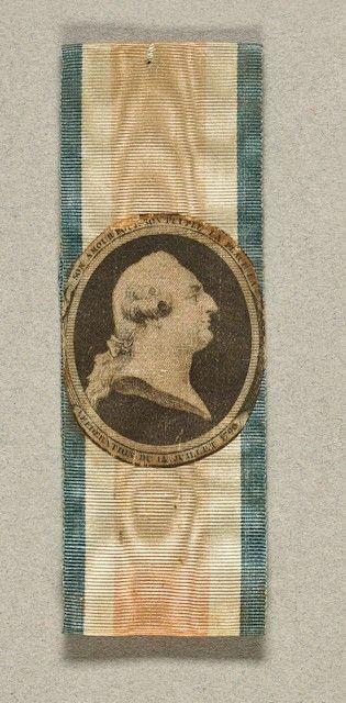 Brassard tricolore en tissu, orné au centre d'un portrait en grisaille représentant un profil du roi Louis XVI, le visage tourné vers la droite, entouré de l'inscription « Son amour pour son peuple l'a placé là - Fédération du 17 juillet 1790 ». En l'état. H.: 2 cm - L.: 11 cm.