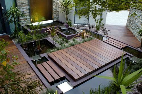 A wooden bridge made of laminate flooring over a stream filled with Koi adds a beautiful touch to any outdoor sitting area. Click on pin to view mapping with the garden industry.