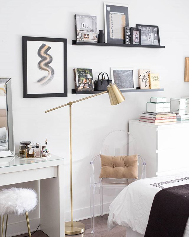 black, white, and gold shelves styling with a ghost chair, gold floor lamp and abstract art.