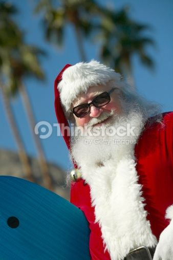 Stock Photo : Father Christmas Holding a Surf Board with Palm Trees in the Background